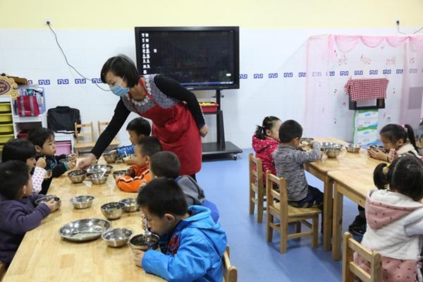 教师为托小班幼儿送餐